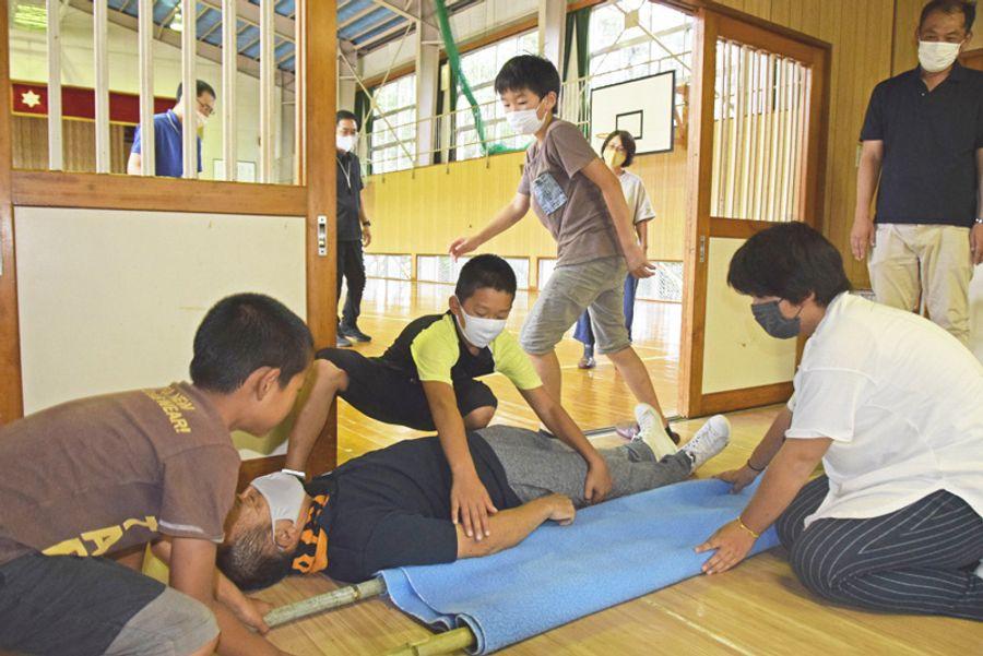 即席の担架を作る児童ら(土佐清水市の幡陽小学校)