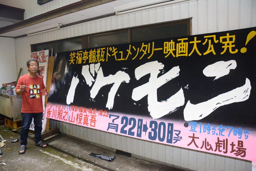 「バケモン」の看板を描き上げた小松秀吉さん(安田町の大心劇場)