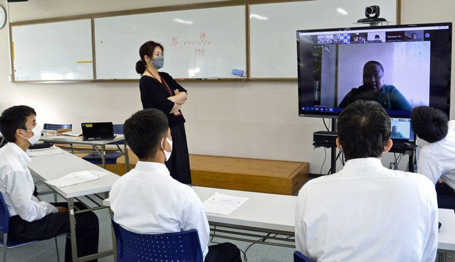 自分たちの防災活動を留学生に説明する大方高校の生徒ら(黒潮町入野の同校)