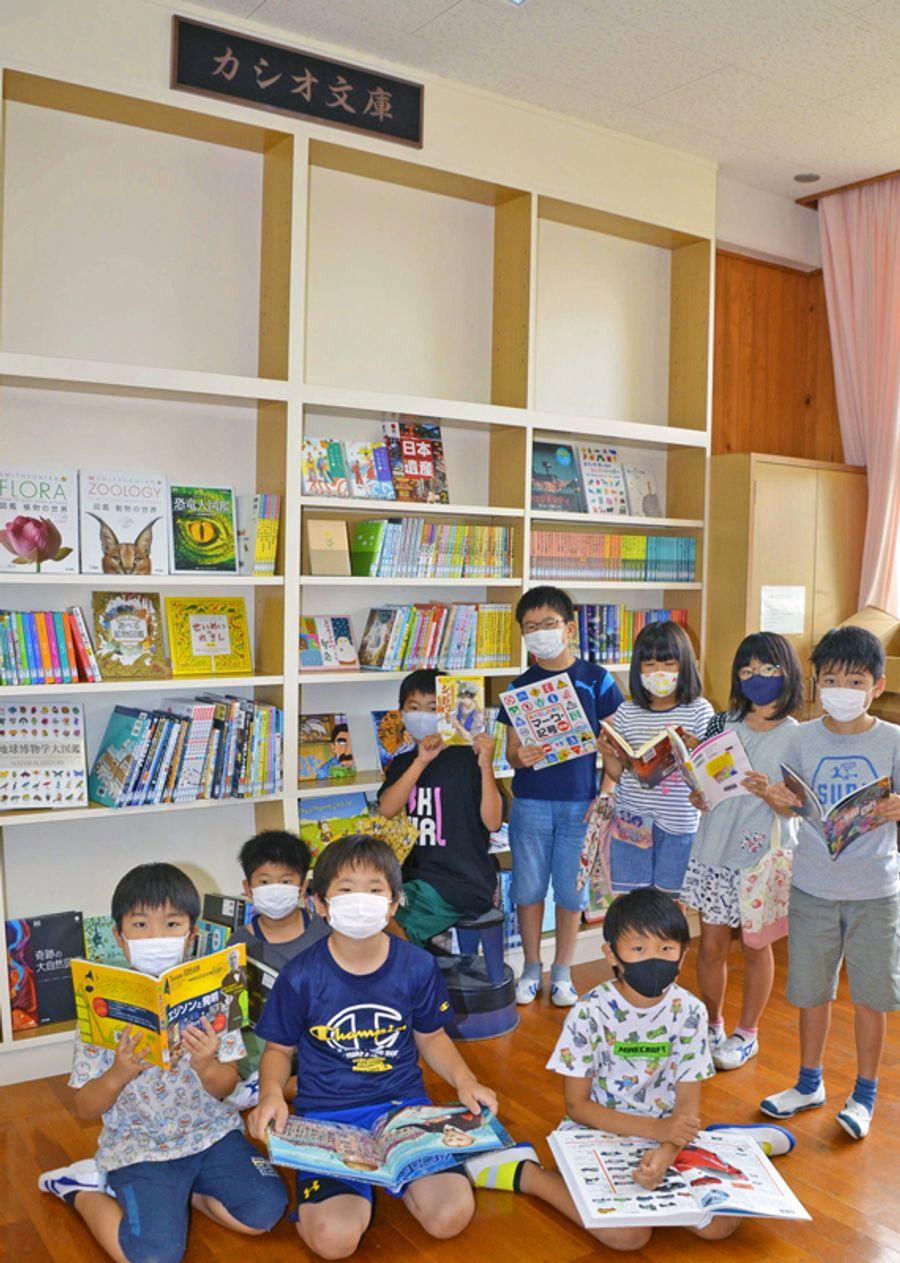 「カシオ文庫」の前で寄贈された本を開く児童(南国市久礼田の久礼田小学校)