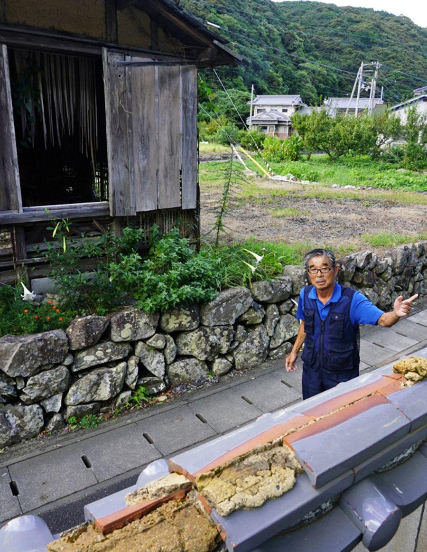 「いつ人が流されてもおかしくなかった」と豪雨を振り返る岡林秀明さん。救出のためはしごを掛けた自宅の塀=手前=は壊れた当時のままだ(大月町周防形)