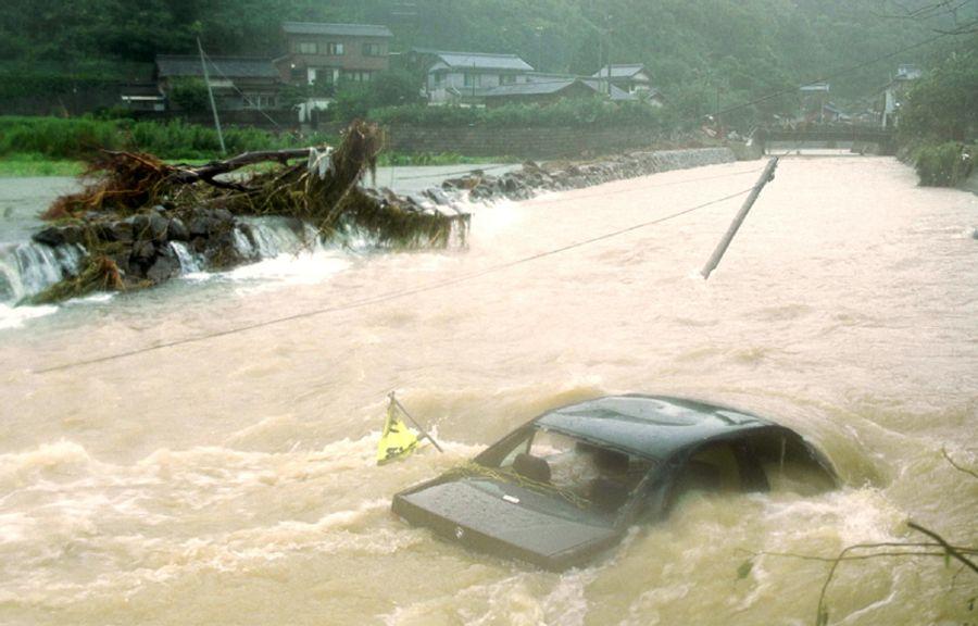 断続的に降り続いた雨で水かさが増し、車ものみ込んだ周防形川。隣接する田畑からもとめどなく濁流が流れ込む(2001年9月7日午前8時ごろ、大月町周防形)