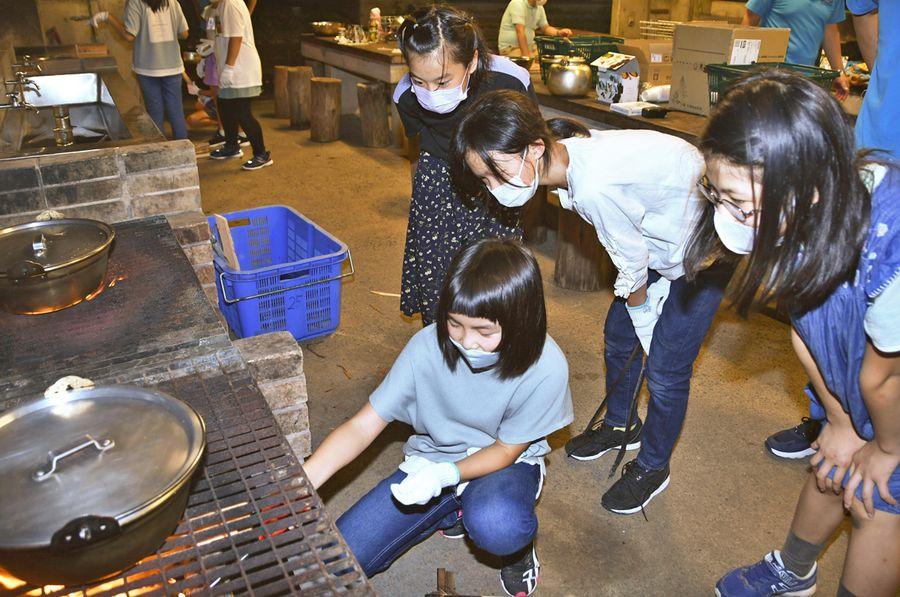 防災キャンプで火をおこして湯を沸かす児童ら(室戸市の室戸青少年自然の家)