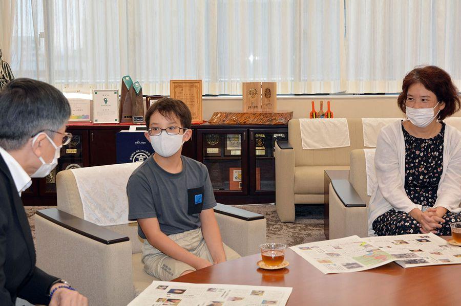 岡﨑誠也市長=左=に平和活動の取材成果を報告する向井さん親子(高知市役所)